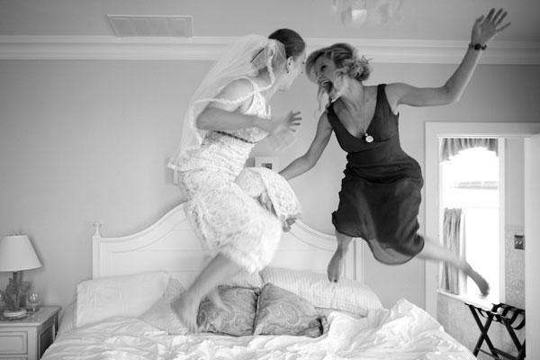 Novia y dama de honor saltando en la cama